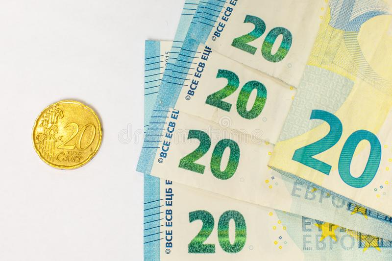 Several banknotes of 20 euros and a coin of 20 cents. The concept of opposing large and small earnings, saving or spending money royalty free stock photography