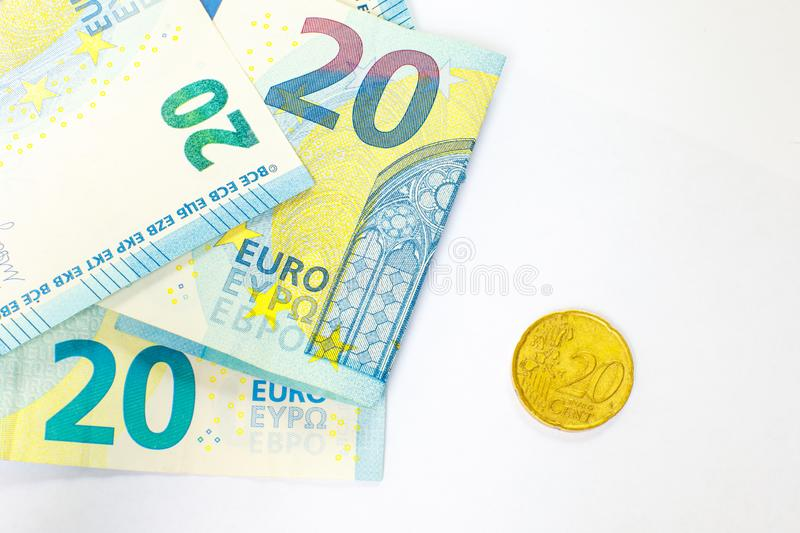 Several banknotes of 20 euros and a coin of 20 cents. The concept of opposing large and small earnings, saving or spending money royalty free stock photos