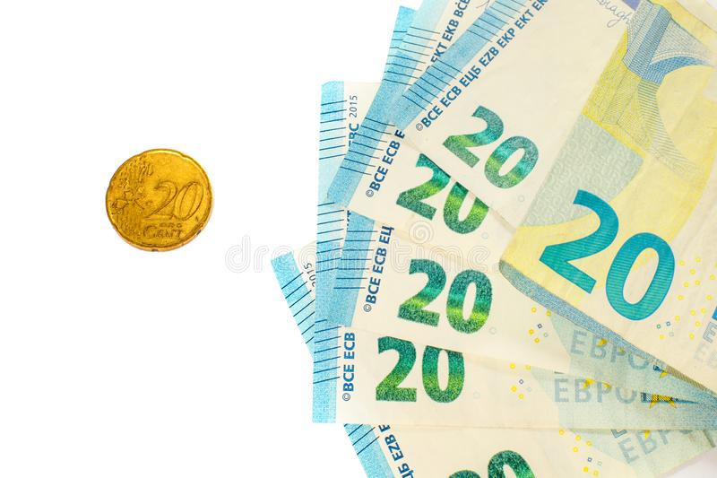 Several banknotes of 20 euros and a coin of 20 cents. The concept of opposing large and small earnings, saving or spending money. stock photos