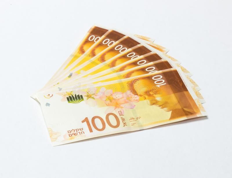 Several banknotes of a new type with a portrait of poet Lea Goldberg worth 100 Israeli shekels isolated on a white background royalty free stock photography