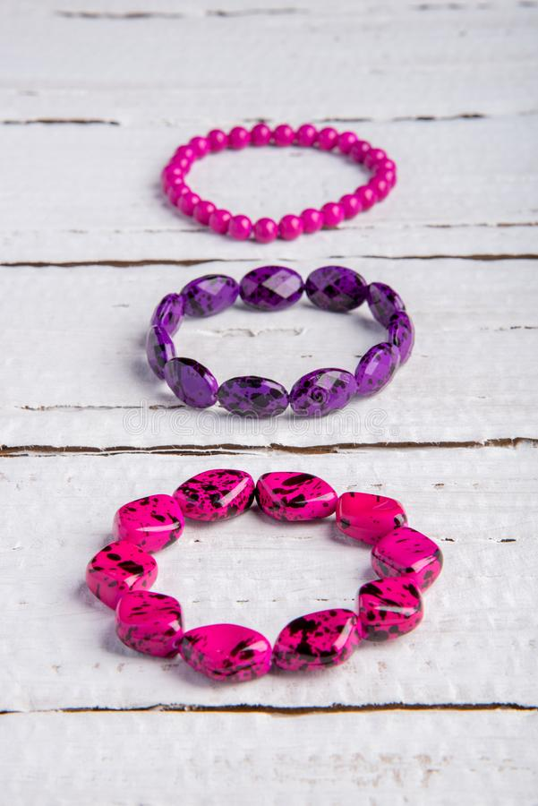 Several beautiful bracelets of beads and stones of pink and purple on a wooden background royalty free stock images