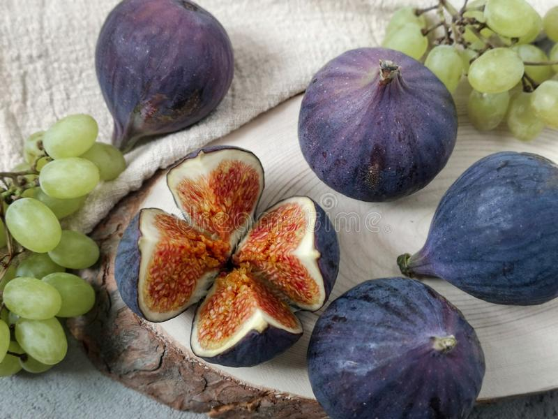 Several berries of figs and small bunches of grapes lie on a table on a circle of natural sawn wood and a linen napkin. stock image