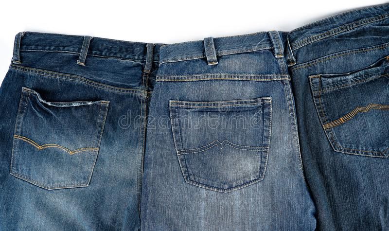 Several blue classic jeans folded in a row. Back pocket royalty free stock images