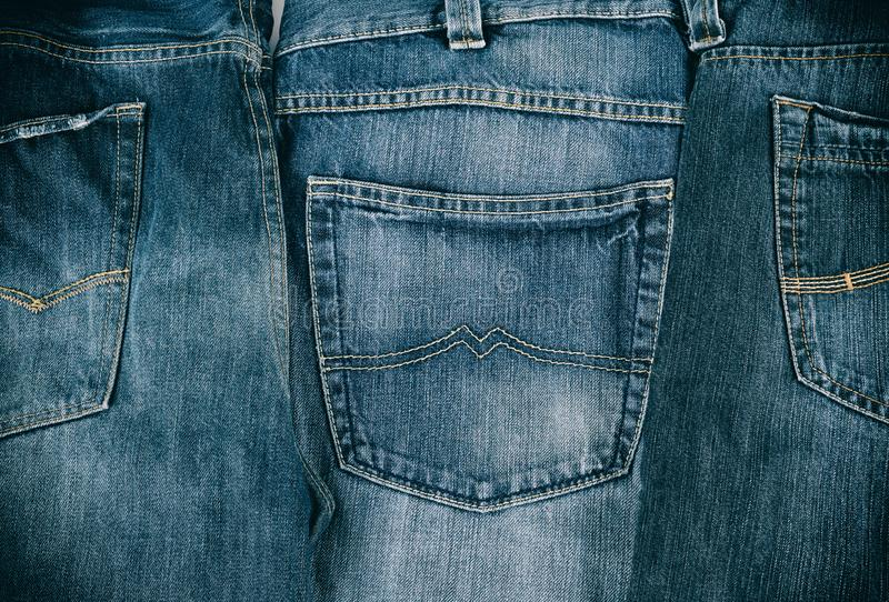 Several blue classic jeans folded in a row. Back pocket royalty free stock image