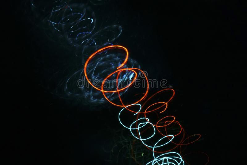 Blue and orange neon glowing spirals on a black background stock illustration