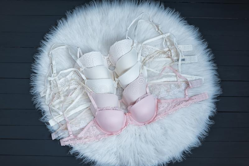 Several bodices with lace on white fur. Pastel shades. Fashionable concept of lingerie.  stock photography