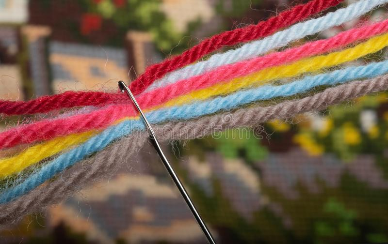 Several bright multicolored woolen threads are pass through the eye of the needle. Close-up royalty free stock image