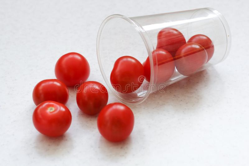 Several bright red ripe cherry tomatoes rolled out of a plastic transparent glass royalty free stock image