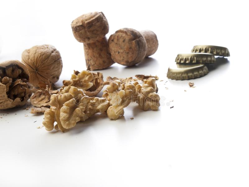 Several broken walnuts with champagne corks and tin caps for bottles. On a white background royalty free stock photos