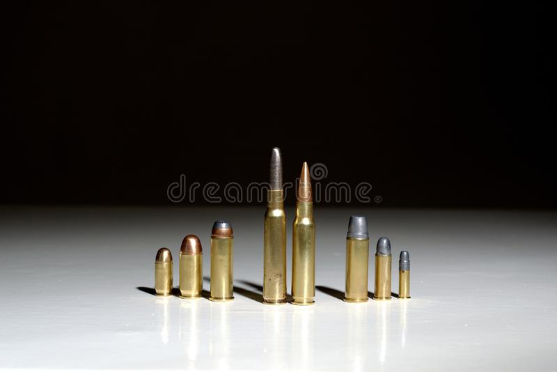 Several bullets of different calibers standing on a white surface with a black background royalty free stock photo