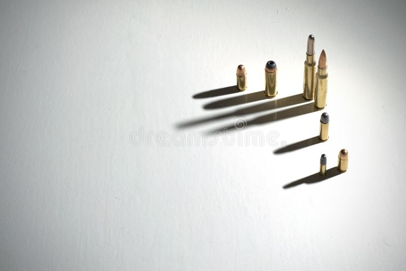 Several bullets standing on a white surface with long, dark, dramatic shadows royalty free stock photo