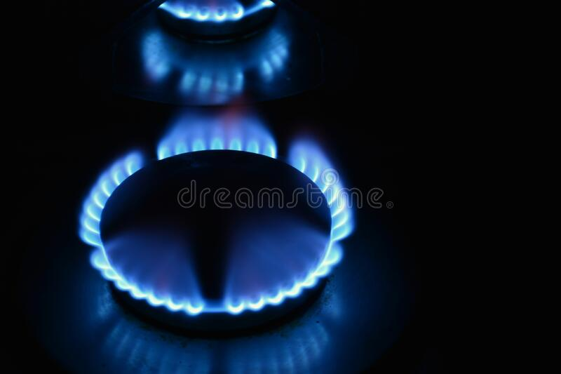 Fuegos encendidos de una hornilla de gas. Several burners lit in the dark with flame of a butane gas burner royalty free stock images