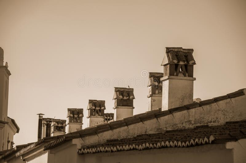 Several chimneys over rooftop of old house stock images
