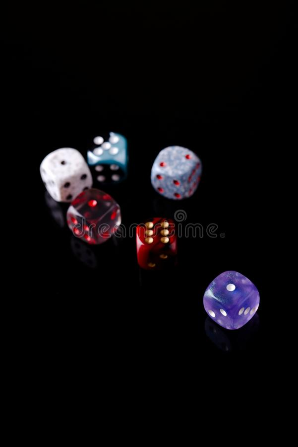 Several color dices on black board. Vertical photo with several color dices which are placed on black board with nice reflections. Few dices are semi-transparent royalty free stock photography