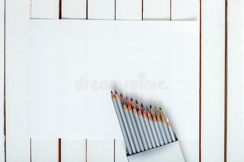 Several colored pencils on the paper. Several colored pencils which are looking out of a pack which are on the sheet of paper lying on a wooden table from white stock photography