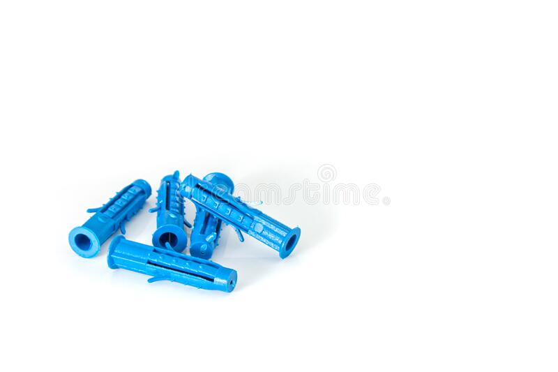 Several construction dowels for the screws lie erratically close-up on a white background royalty free stock photo
