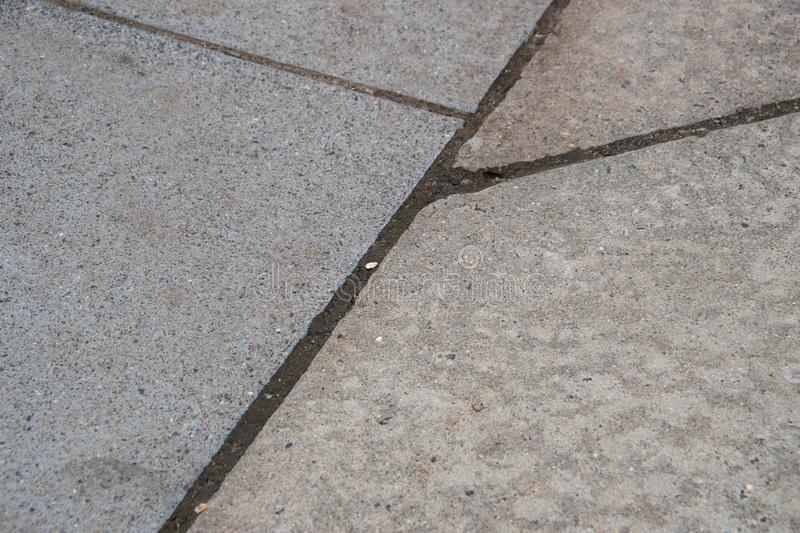 Several cracks between blocks of concrete sidewalk. Some are perpendicular and one goes off on an angle. royalty free stock image