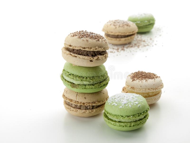Several cream and green colored macarons with chocolate scratches. Are on a white background stock photography