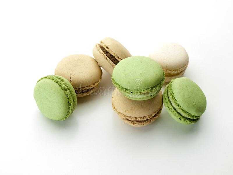 Several cream and green macarons with chocolate scratches. Are on a white background viewed from above royalty free stock photo