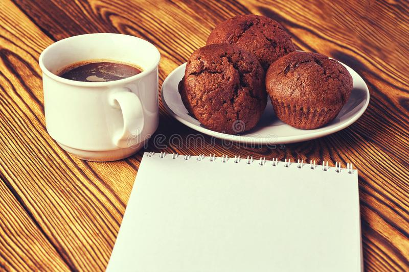 Several dark chocolate dough muffins with a cup of coffee and a notepad on a wooden table royalty free stock images