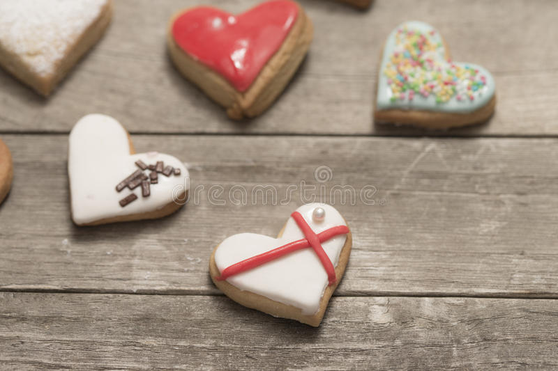 Several delicious cookies with icing. Baked valentine's hearts on wooden background royalty free stock images