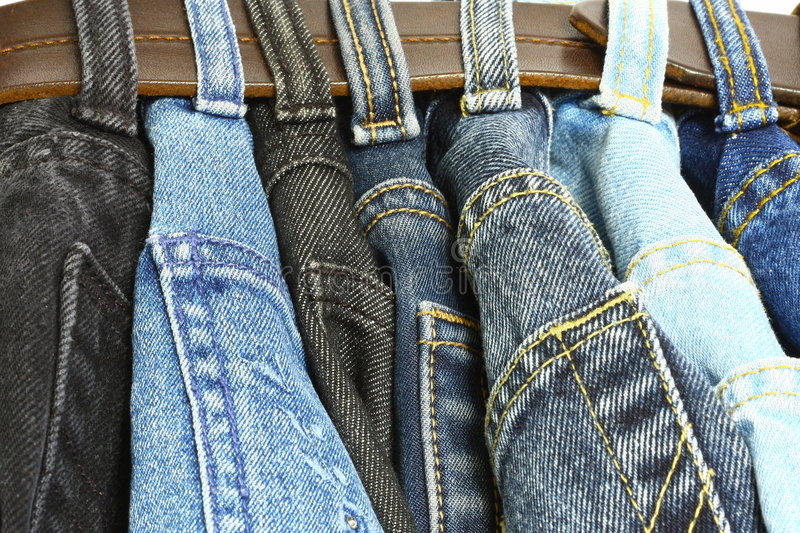 Several denim pants. Some denim pants in a belt stock image