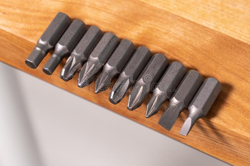 Several different screwdriver tips on the edge of solid wood workbench stock images