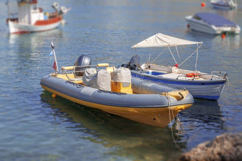 Several docked vintage wooden motor boat at sea royalty free stock photo