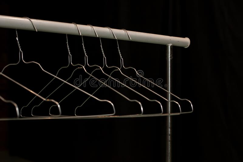 Several empty metal hangers on the holder, everything is sold, the store is closed royalty free stock photography