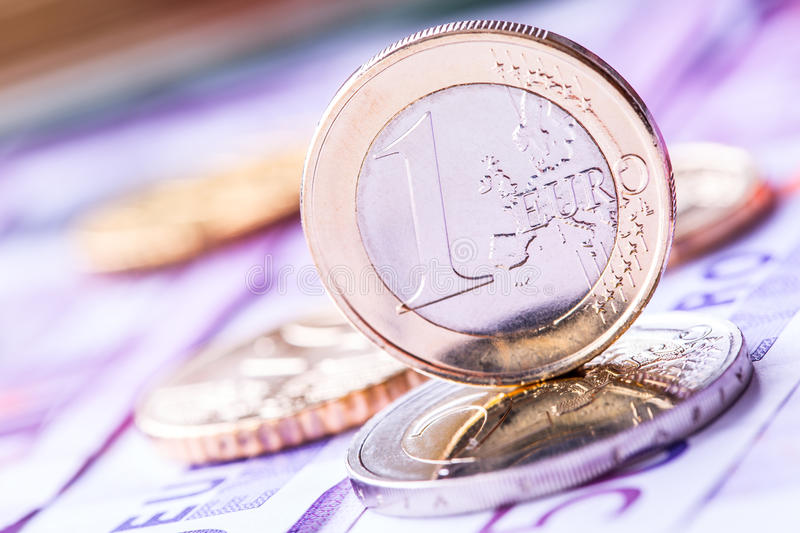 Several 500 euro banknotes and coins are adjacent. Symbolic photo for wealt. Euro coin balancing on stack with background of banknotes. Money concept royalty free stock photos