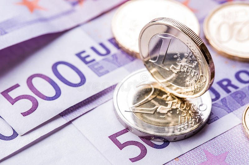 Several 500 euro banknotes and coins are adjacent. Symbolic photo for wealt.Euro coin balancing on stack with background of bankno royalty free stock image