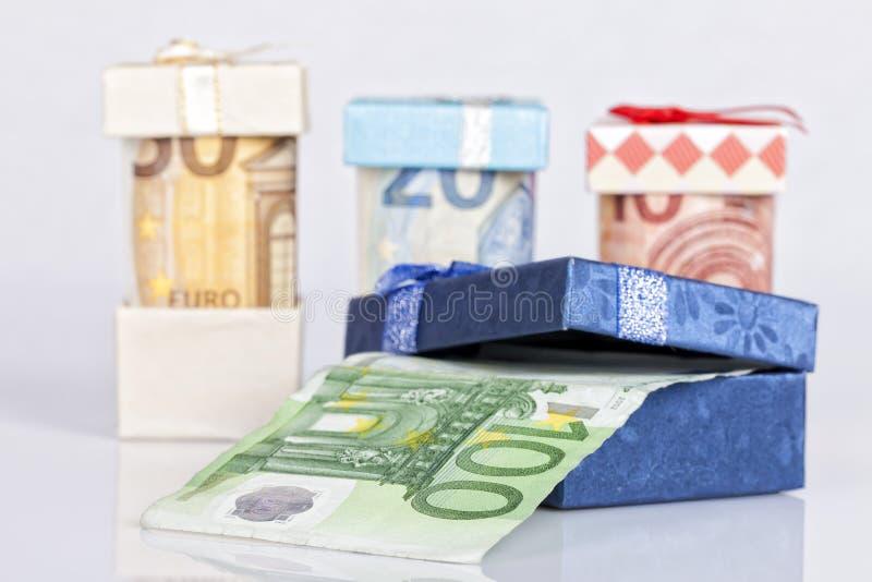 Several euro bills inside gift boxes on white stock image