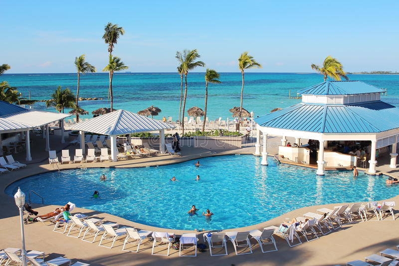 Several families enjoying their holidays time in the swimming pool of a luxury hotel resort placed close to a caribbean beach stock photo