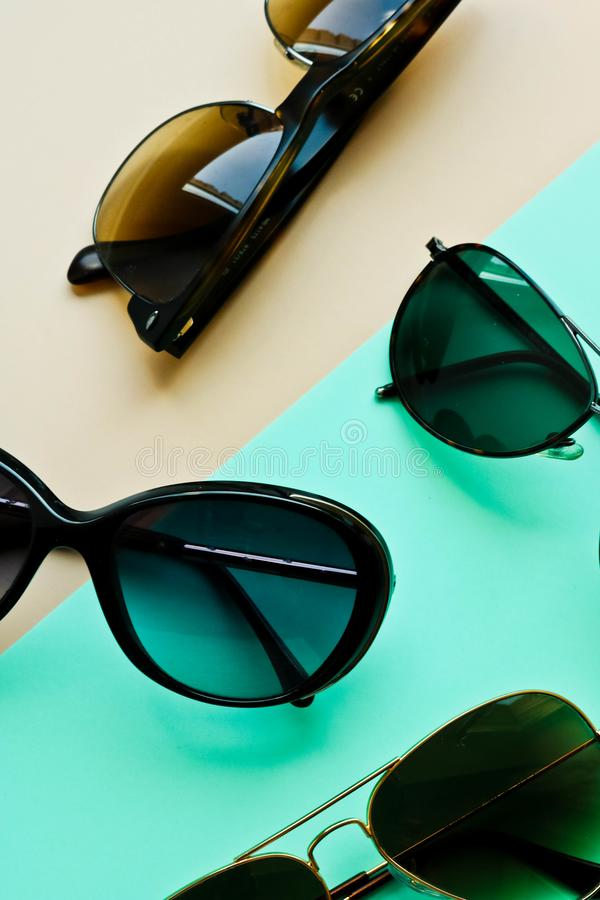 Several fashion sunglasses on colorful duotone background royalty free stock photos