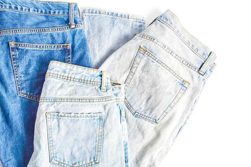 Several folded pairs of jeans in various shades of blue and light blue. On a white background stock image