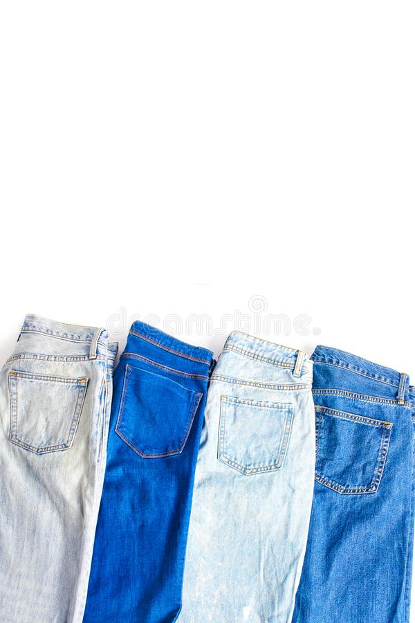Several folded pairs of jeans in various shades of blue and light blue on a white background. Flat lay, copy space, vertical frame stock images