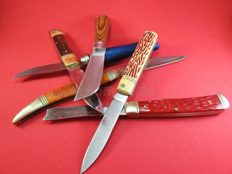 Several folding pocket knives, with the blade exposed. stock images