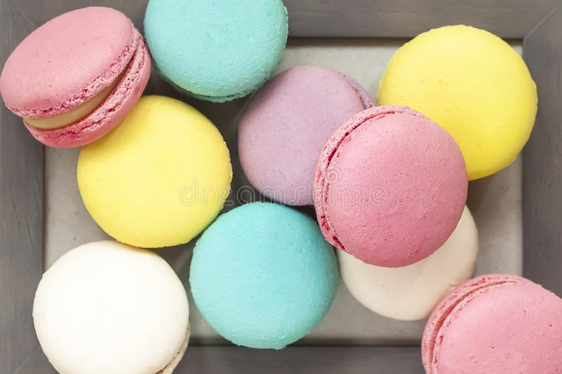Several fresh colorful macarons of different tastes in wooden frame close-up, top view, unusual abstract sweet art stock photo