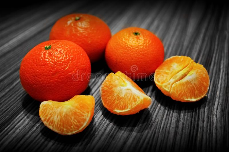 Several fresh ripe tangerines and peeled tangerine slices on wooden surface stock image