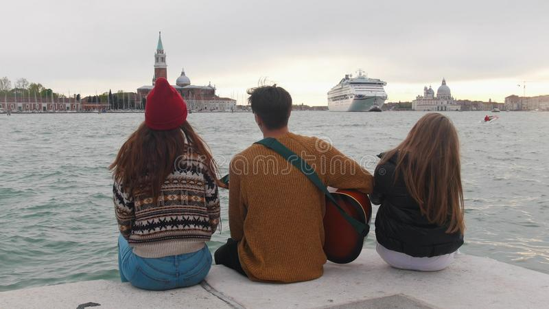 Several friends are sitting on the embankment and chatting with guitar music. royalty free stock images
