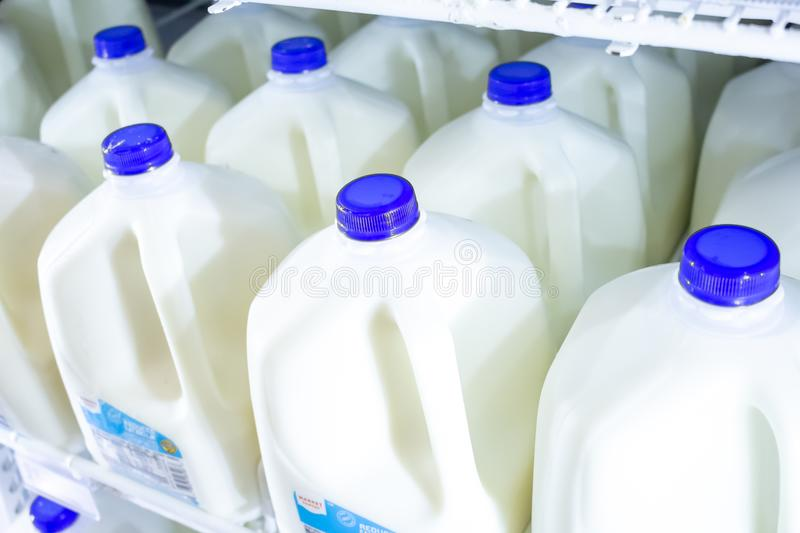 Several gallon jugs of milk at the store stock photography
