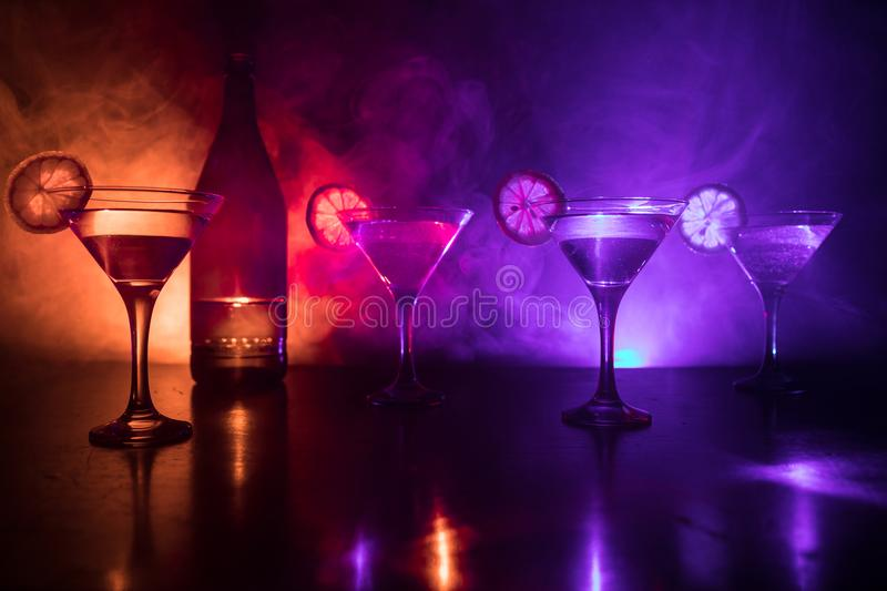Several glasses of famous cocktail Martini, shot at a bar with dark toned foggy background and disco lights. Club drink concept. royalty free stock photos
