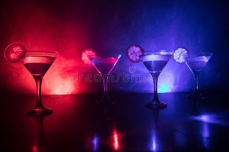Several glasses of famous cocktail Martini, shot at a bar with dark toned foggy background and disco lights. Club drink concept. stock images