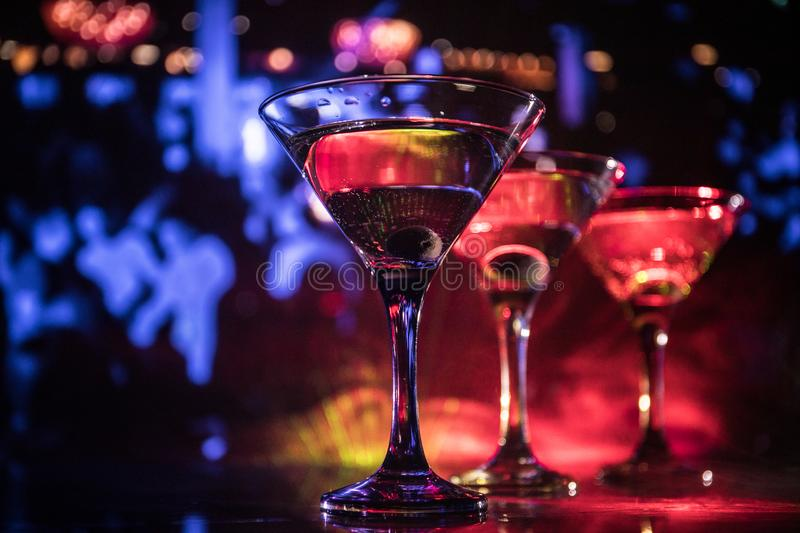 Several glasses of famous cocktail Martini, shot at a bar with dark toned foggy background and disco lights. Club drink concept stock photos