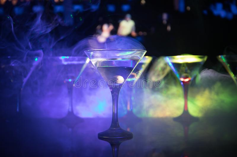 Several glasses of famous cocktail Martini, shot at a bar with dark toned foggy background and disco lights. Club drink concept royalty free stock image