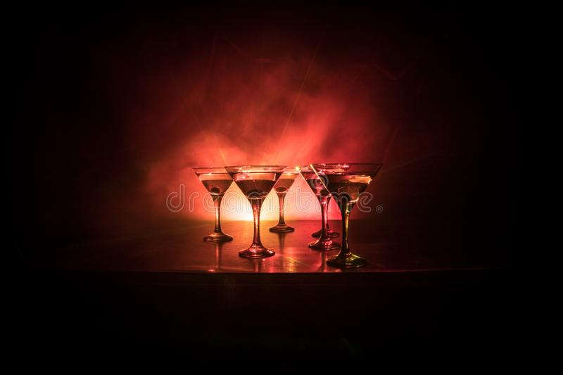 Several glasses of famous cocktail Martini, shot at a bar with dark toned foggy background and disco lights. Club drink concept royalty free stock photography