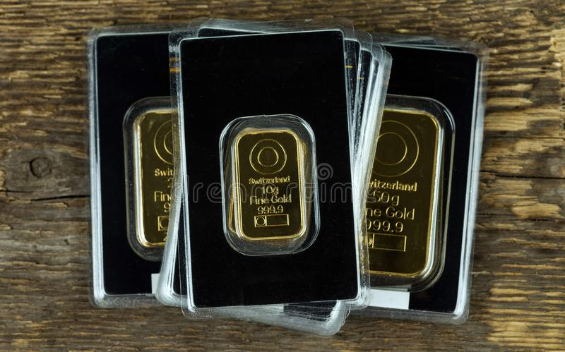 Several gold bars of different weight in plastic packaging on a wooden background royalty free stock photo
