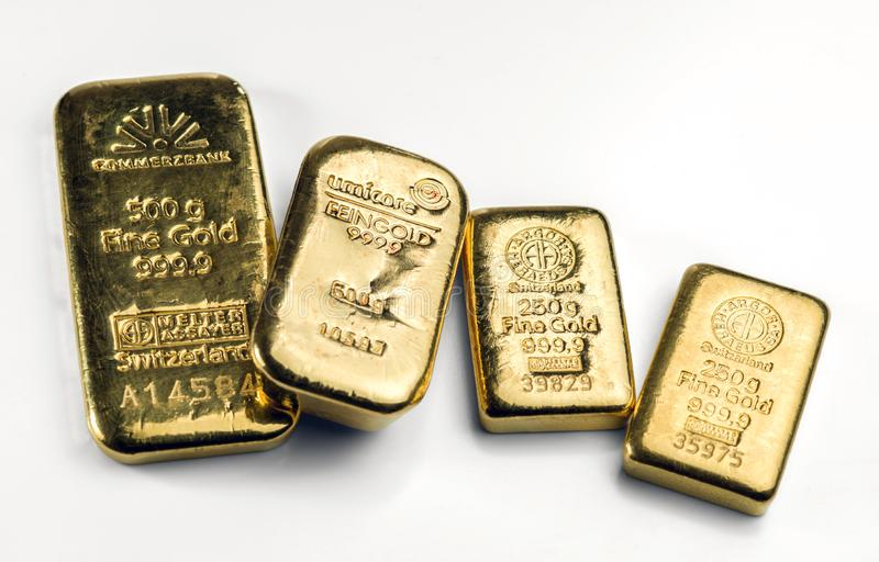 Several gold cast bars of different weights and different manufacturers lie on a white surface royalty free stock photo