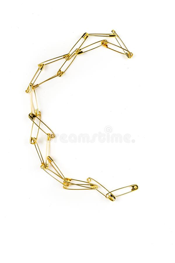 Several gold safety pin chain spread in a moon shape royalty free stock photo