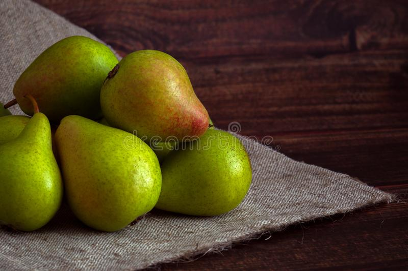 Several green pears on a homespun napkin on a wooden table royalty free stock photos